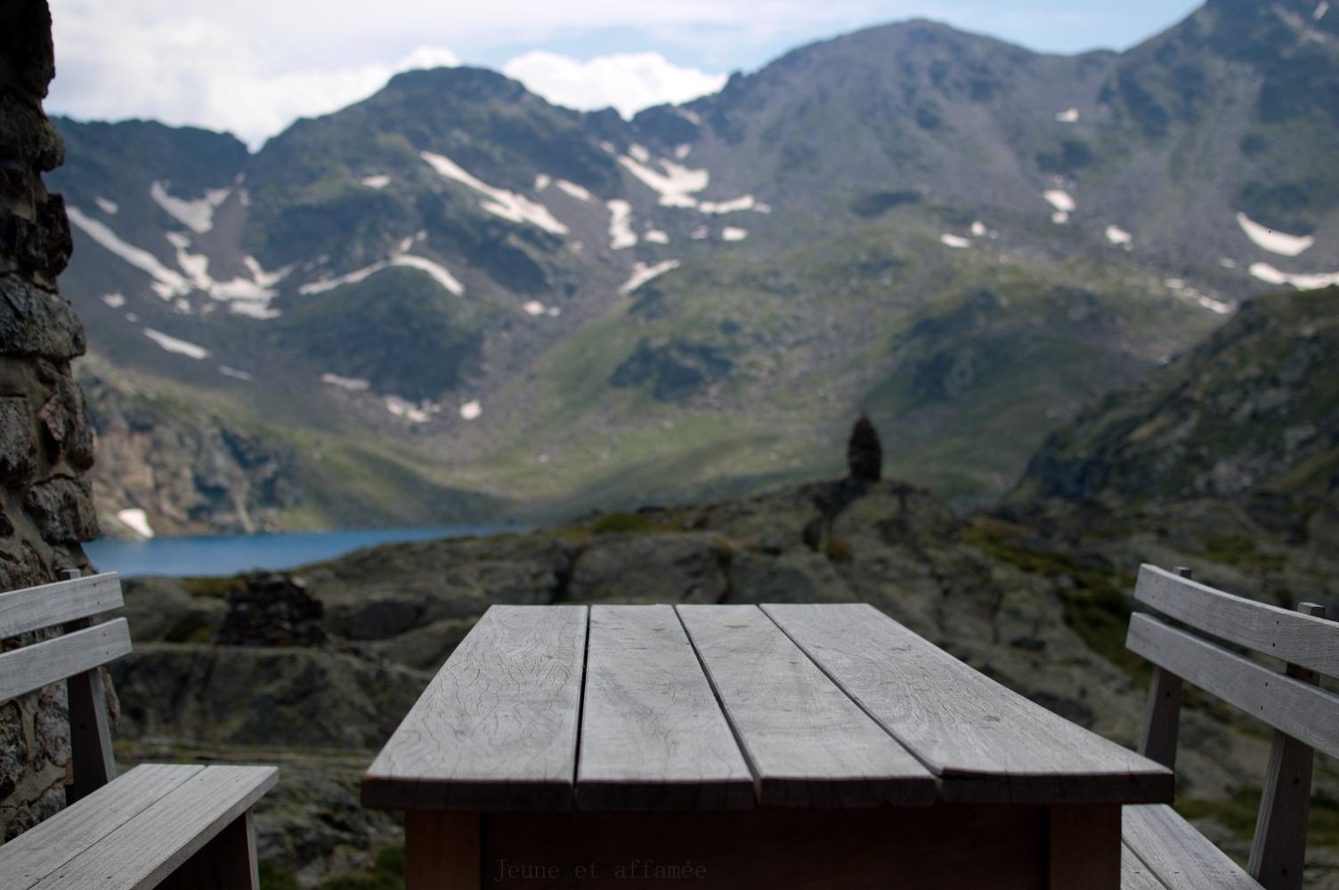 Table avec vue sur l'étang Fourcat et la montagne depuis la terasse du refuge