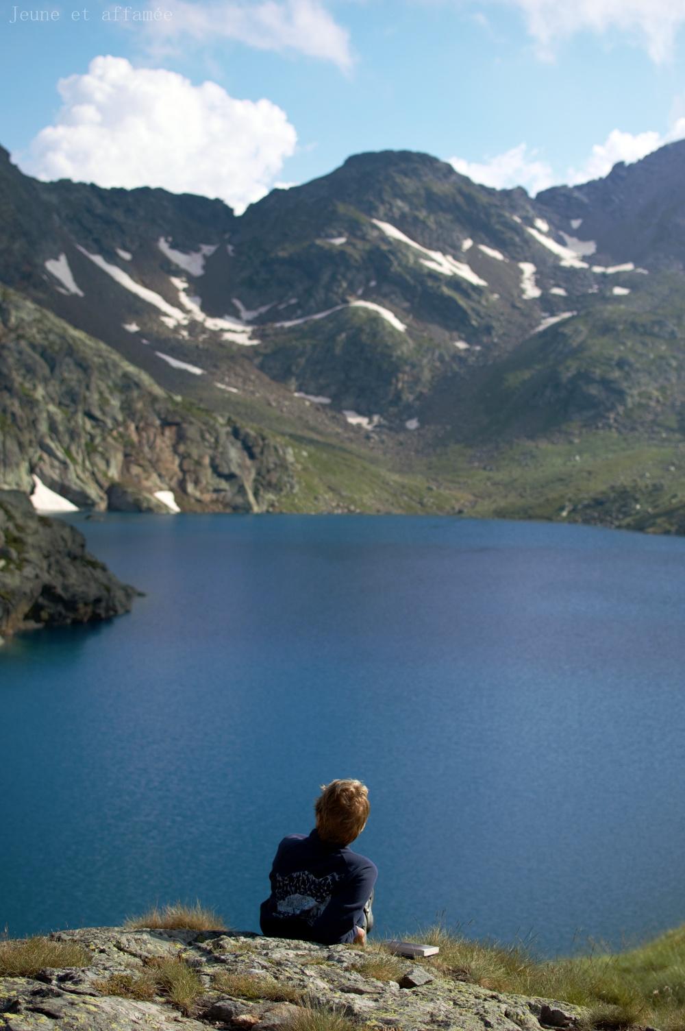 Femme de dos devant l'étang Fourcat, montagnes au fond avec quelques traces de neige